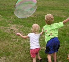 Kids Chasing Bubbles at a Family Picnic