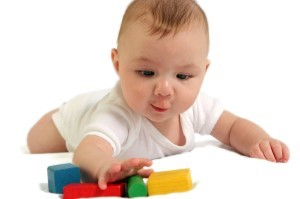 Baby reaching for colorful wooden blocks