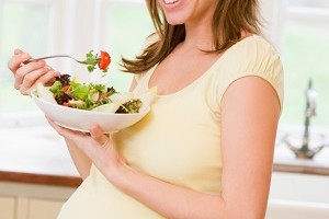 Pregnant woman in kitchen eating a salad smiling