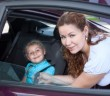 Child sitting in baby car seat and mother helping