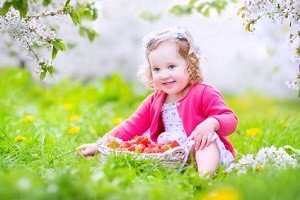 Toddler snack ideas Toddler girl eating strawberry in blooming garden