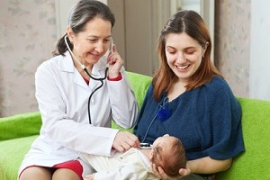mature children's doctor examining newborn