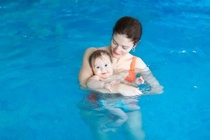 Young mother and her baby enjoying a baby swimming lesson in the