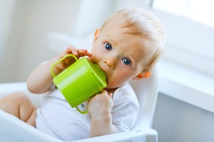 Lovely baby  sitting in chair and drinking from baby cup - Straight from Breast to Sippy Cup: Is it Possible?