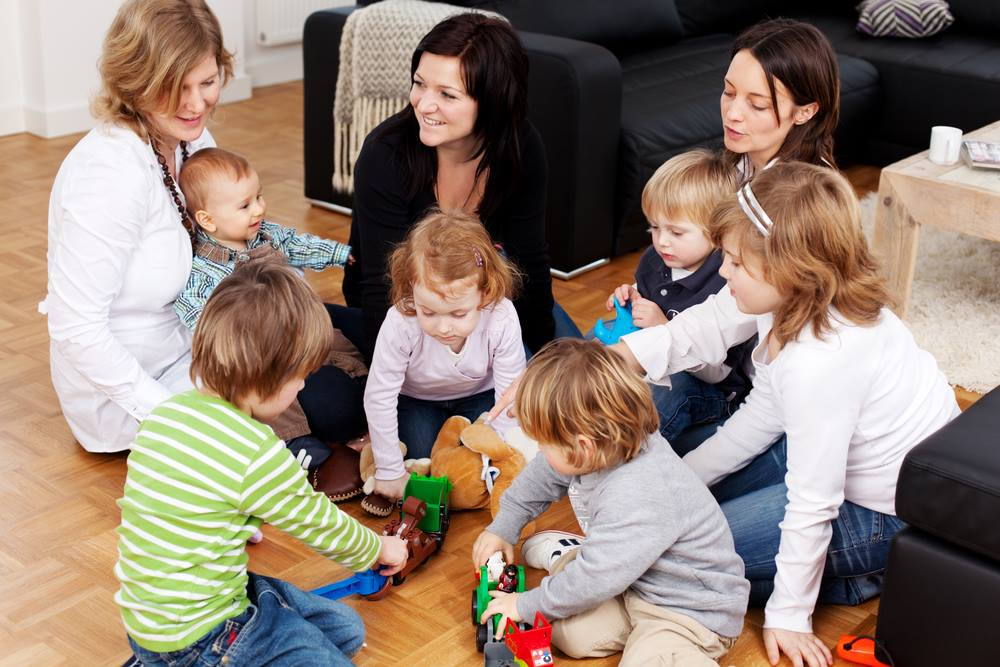 Mums and kids sitting around in a circle in a loungeroom discussing baby on a budget