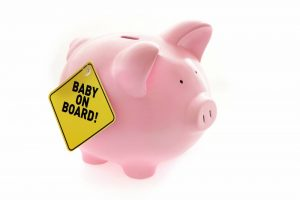 Pink piggy bank showing baby on board sign to reflect having a baby on a budget