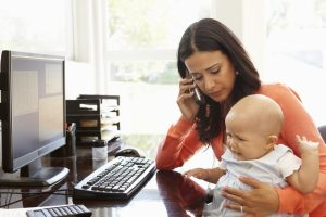 Mother working from home with a baby on her lap