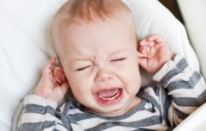 Getting sleep while raising children. Cute little boy crying and holding his ear on a white background