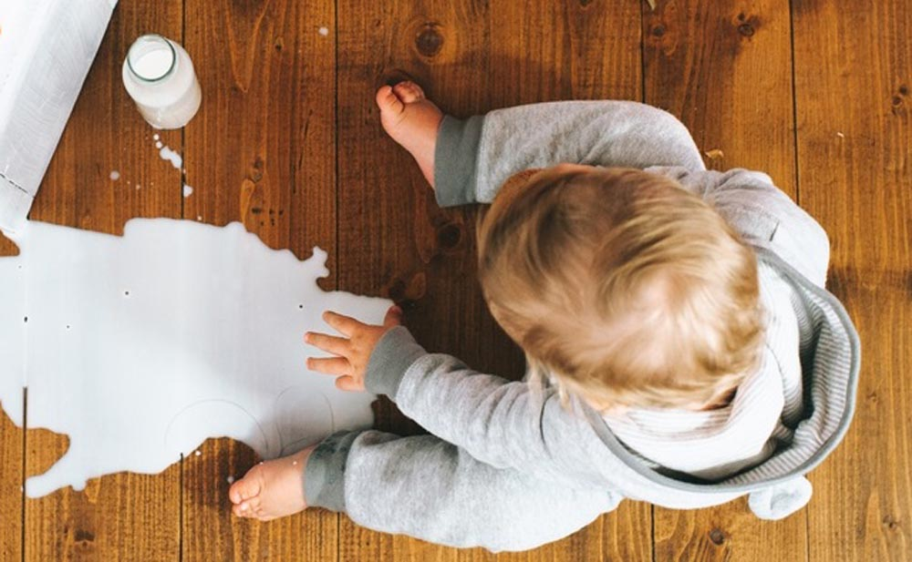 Toddler eating biscuit and spilling his milk drink is all part of raising children