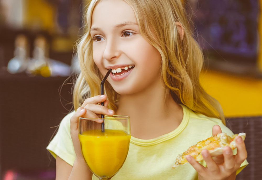 Pretty girls smiling when drinking juice and eating pizza