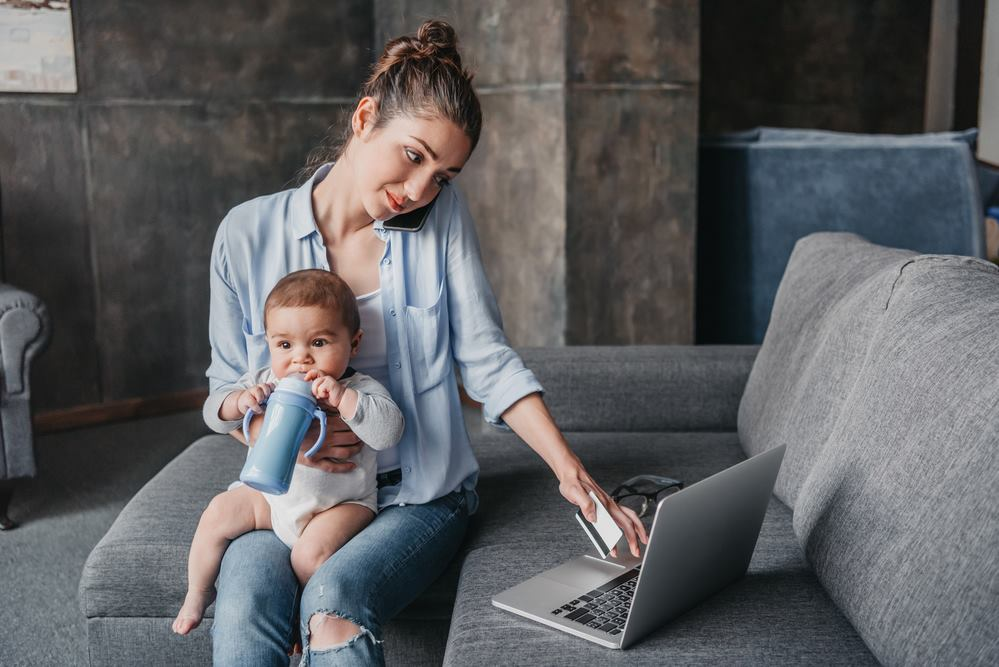 Single mum sitting on lounge holding son and using the computer searching for information on single parent pension