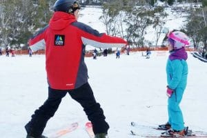 Ski Instructor teaching child to ski